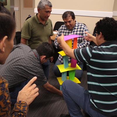 Personas armando una torre de papel