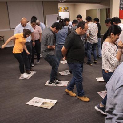 Team-building personas caminando sobre periodicos